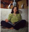 1945-american-actor-lauren-bacall-smiling-and-sitting-cross-legged-on-a-sofa-an-open-book-in-her-lap-photo-by-hulton-archivegetty-images