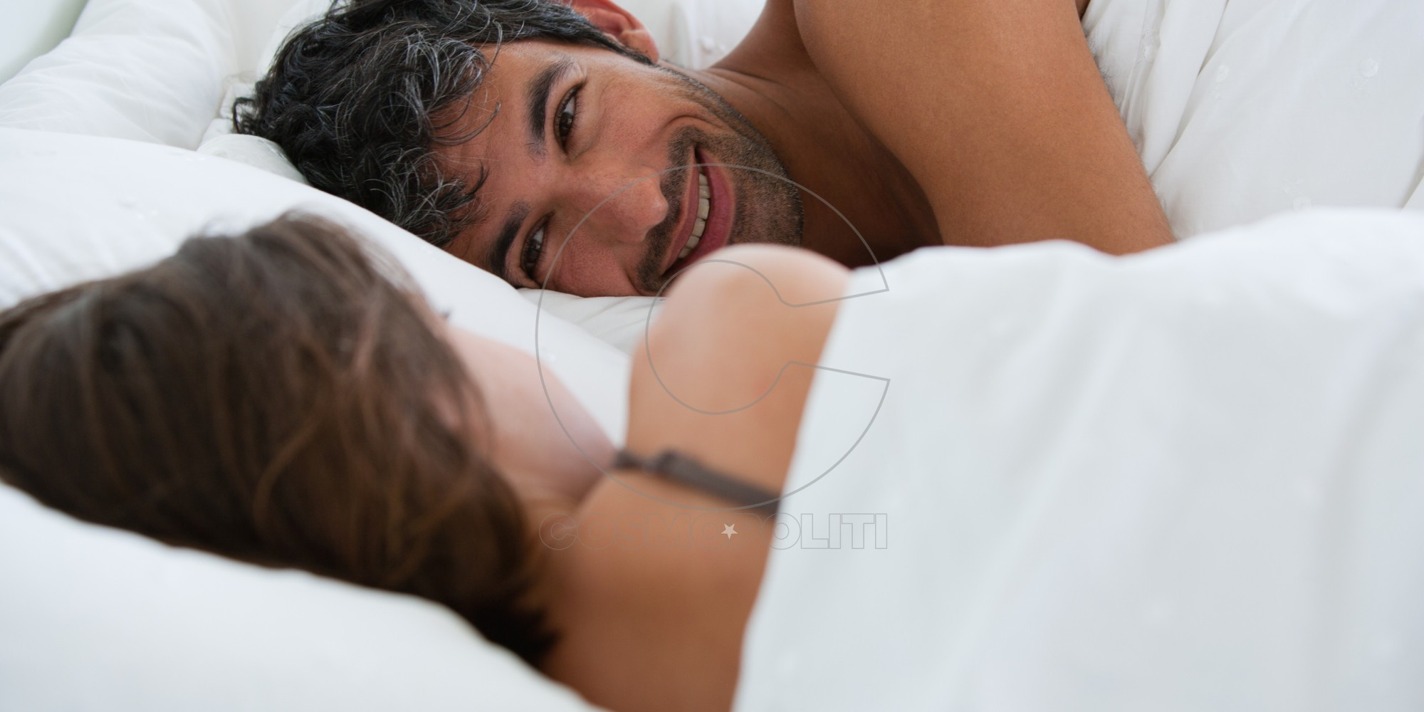 Woman and man lying down in bed