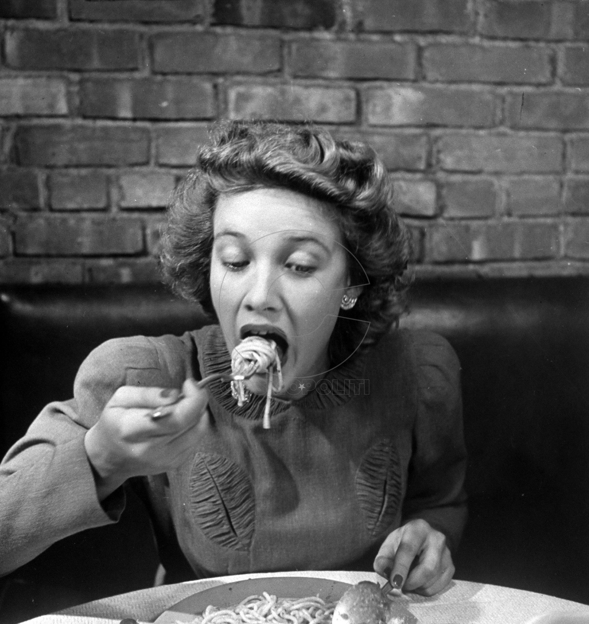 Woman eating spaghetti in restaurant. #4 of sequence of 6.
