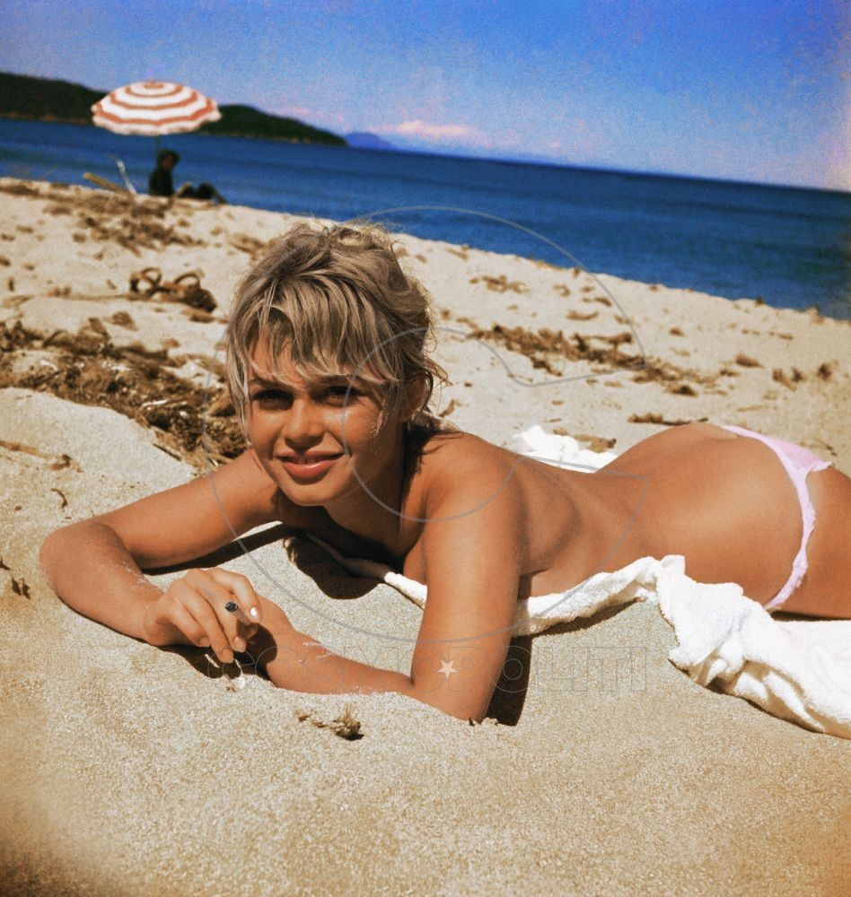 Original Caption: Brigitte Bardot, originally Camille, Javal, actress pictured here on a twel, sunning on the beach.