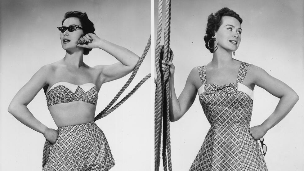Circa 1950 A woman modeling two plaid beach outfitsone consisting of puffed shorts and a bra top and the other of a short sundress with a bow at the neck