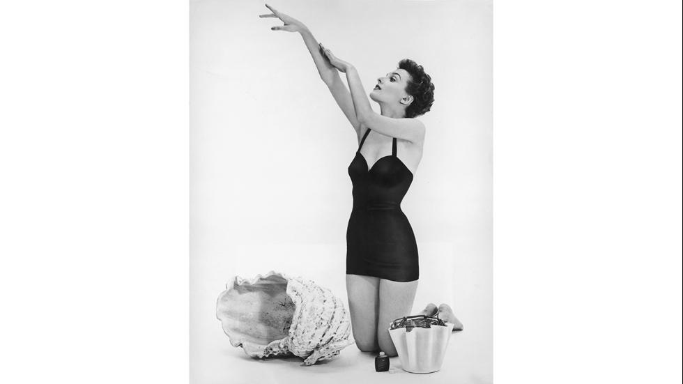 Circa 1950Actress Donna Wallace applies sun tan lotion before a day on the beach