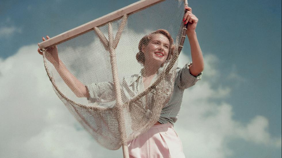 Circa 1955A model wearing white shorts and green gingham shirt poses with a fishing net on a pebble beach Great Britain