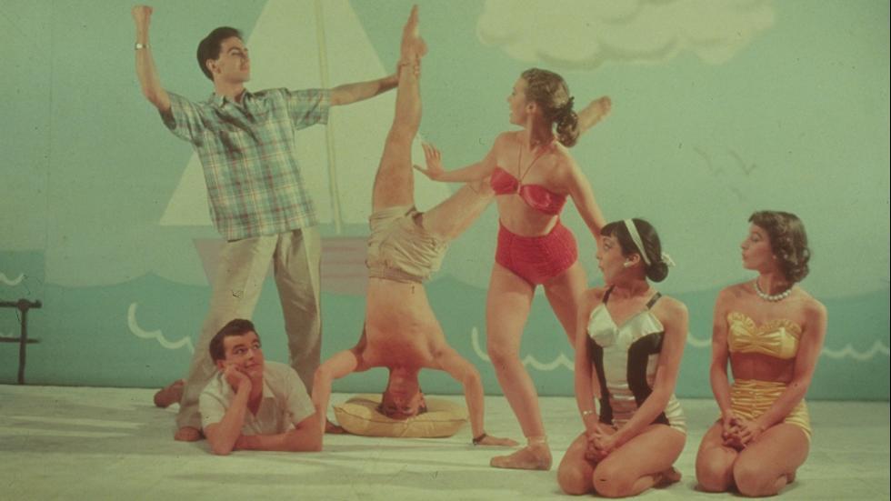 Circa 1955Models wearing bikinis and beachwear against a back drop of a sailing boat