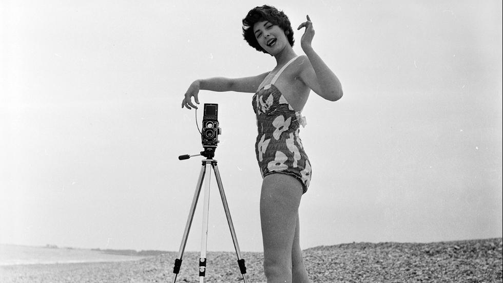 July 1956Fashion model Darien Leigh takes a picture of Valerie Drew on the beach