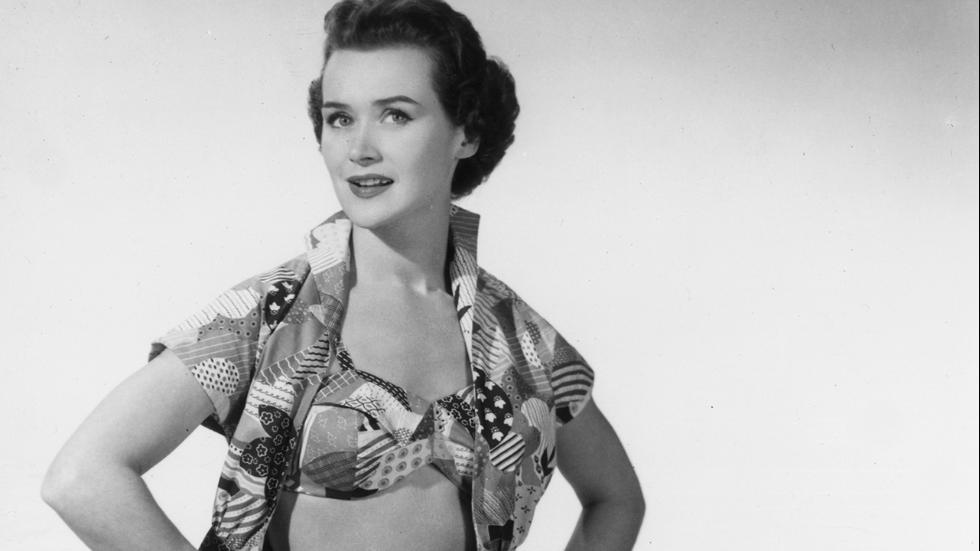 November 1954 A woman modeling a beach outfit with a patchwork designconsisting of shorts, a bra top and co-ordinated shirt