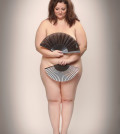 Retro picture of a naked overweight woman with oriental fan.