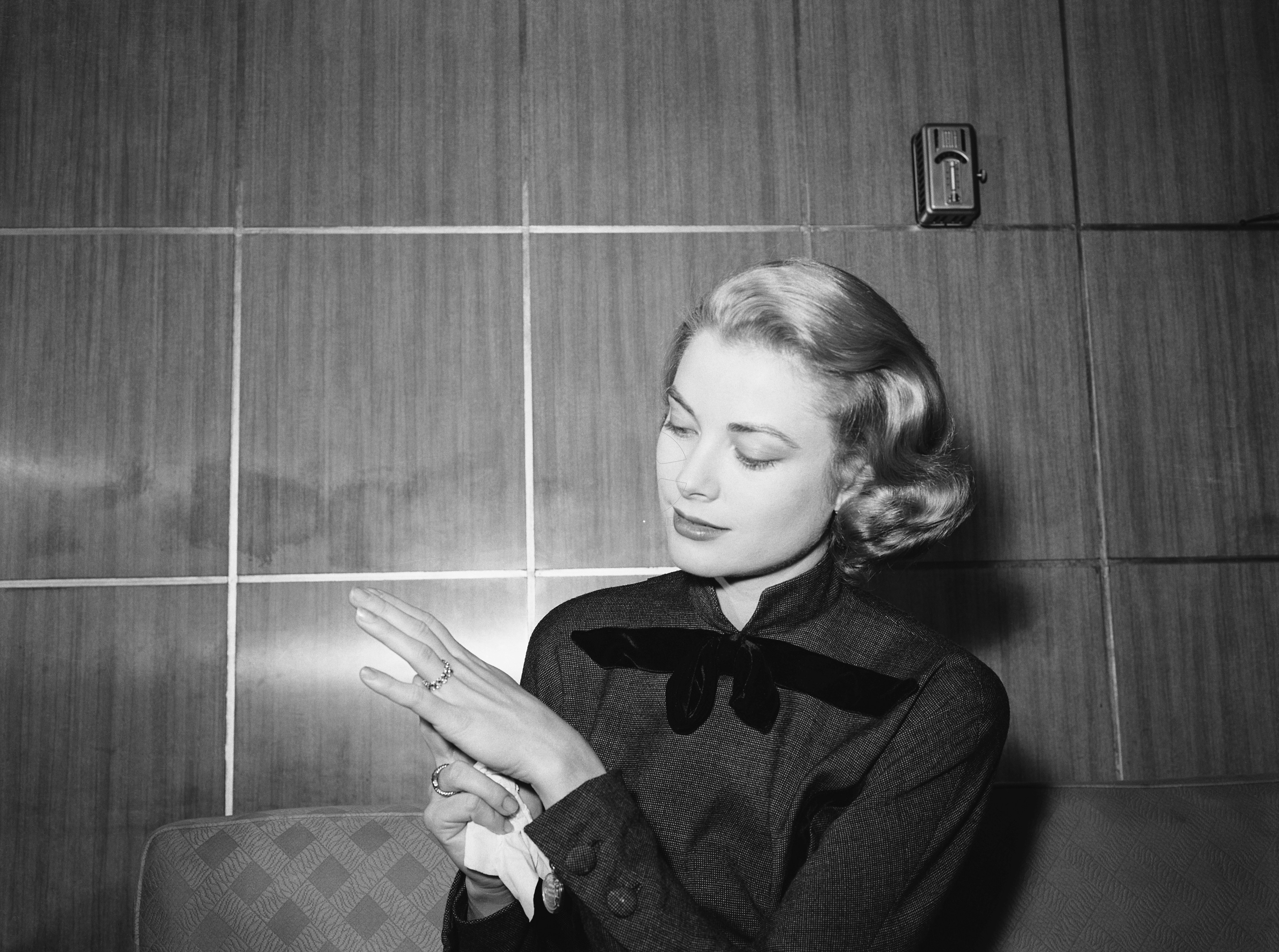 Original caption: 1/10/1956-Chicago, IL: Film actress Grace Kelly, en route to Hollywood for movie work, strikes a pose to show off the engagement ring given her by Prince Rainier III of Monico as she arrives in Chicago. Ther Princess to be posed amiably for photographers on her arrival by train from New York. Rainier will join her on the coast next month, and they will be wedd after her film commitments are completed.