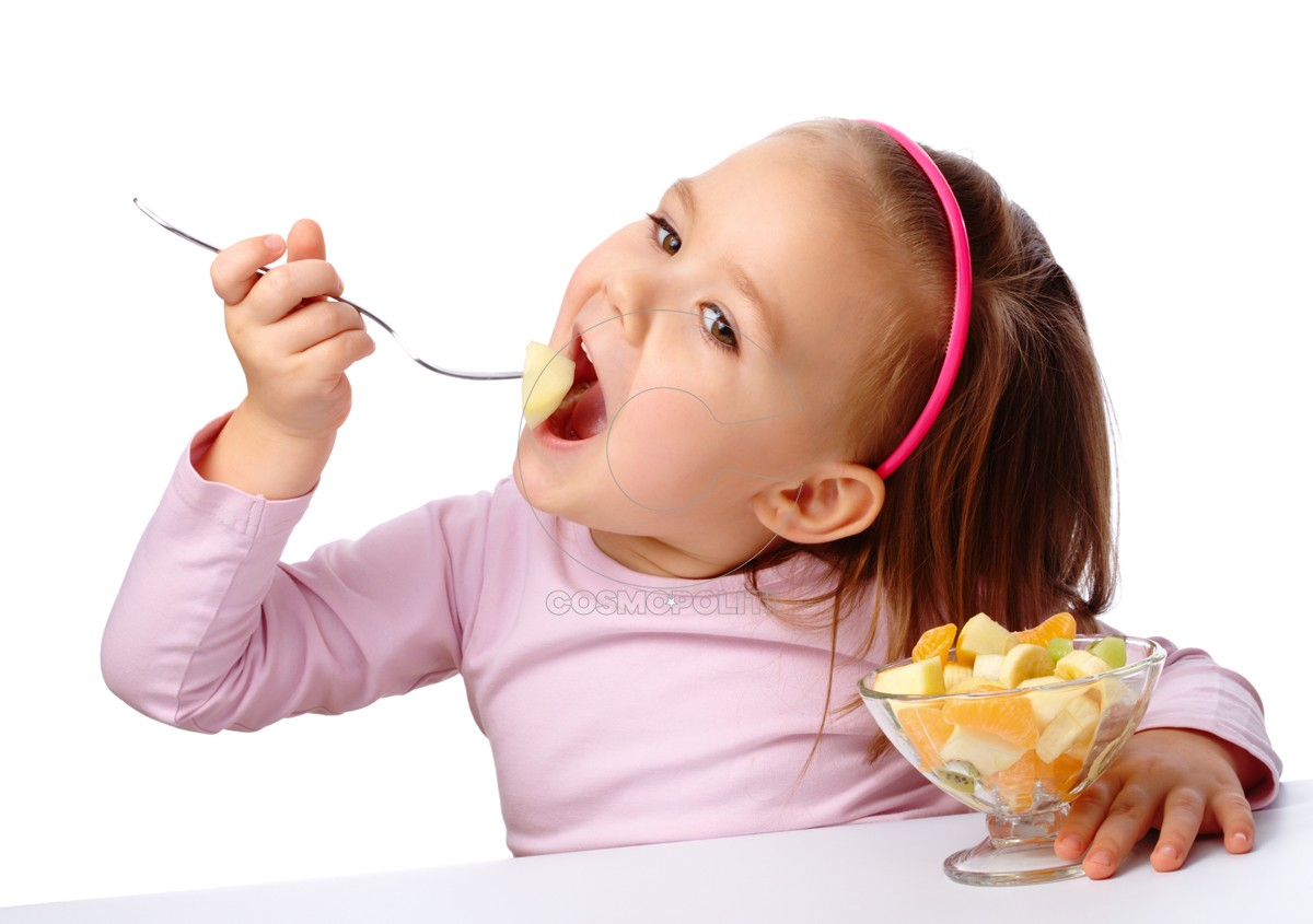 Cute little girl eats fruit salad using fork, isolated over white