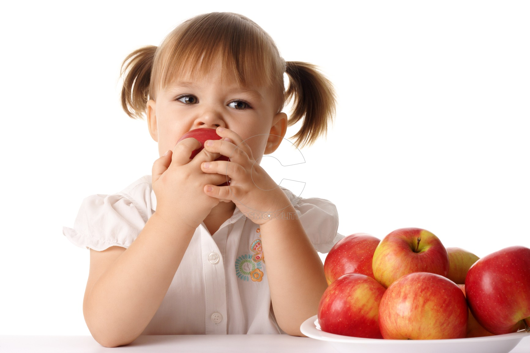 Cute child eats red apple, isolated over white