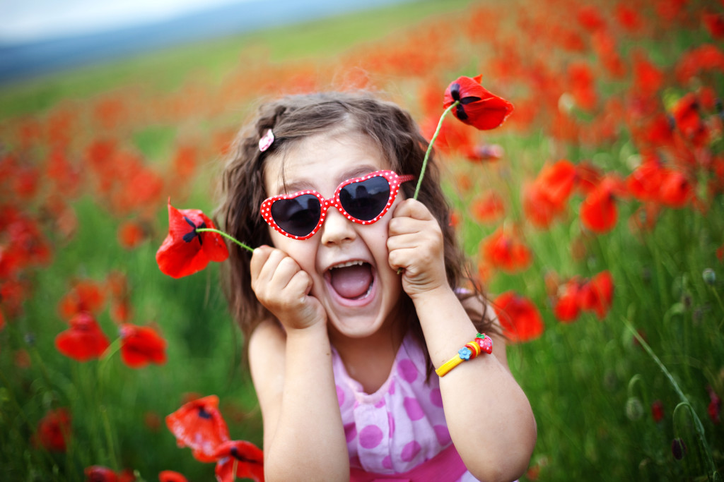 Cute child girl in poppy field