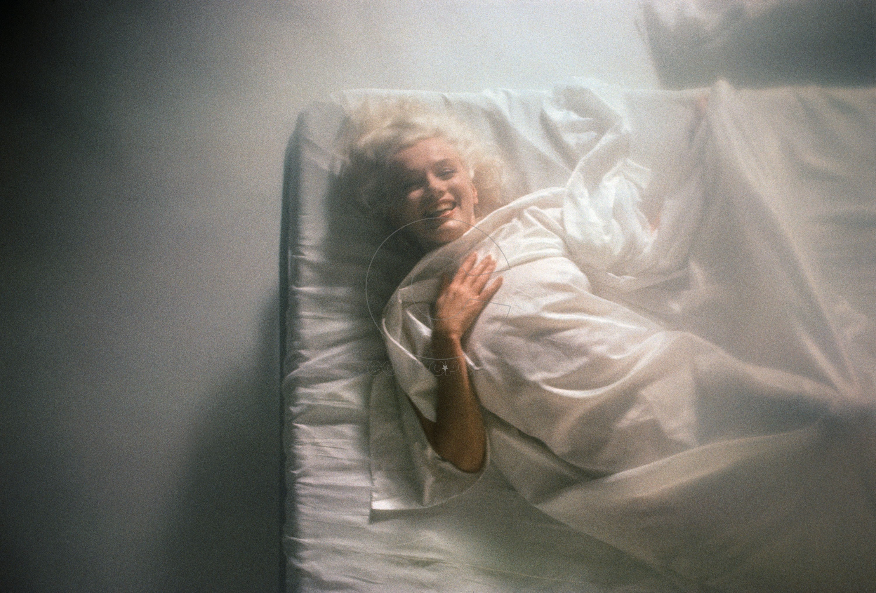 Hollywood, California, USA --- Movie star Marilyn Monroe wraps herself in a white sheet on a bed. --- Image by © Douglas Kirkland/CORBIS