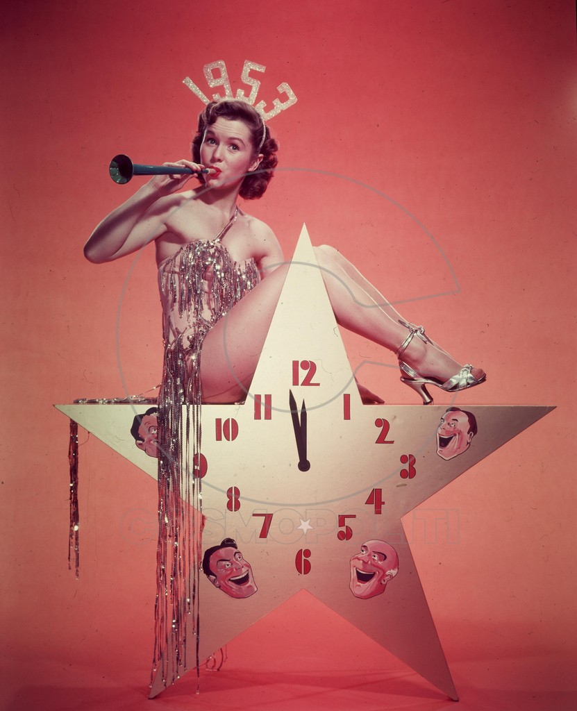 1952:  American actor, dancer and singer Debbie Reynolds, wearing a 1953 tiara and a costume with tinsel, blows a horn while sitting atop a star-shaped clock in a promotional portrait for New Year's Eve.  (Photo by Hulton Archive/Getty Images)