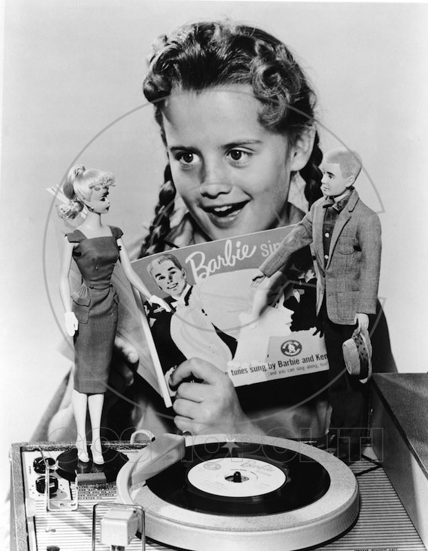 "A girl in pigtails sings along with a 7"" record called 'Barbie Sings' which plays on a portable phonograph player, 1961. Two dolls, Barbie and Ken, stand on the phonograph. (Photo by Hulton Archive/Getty Images)"