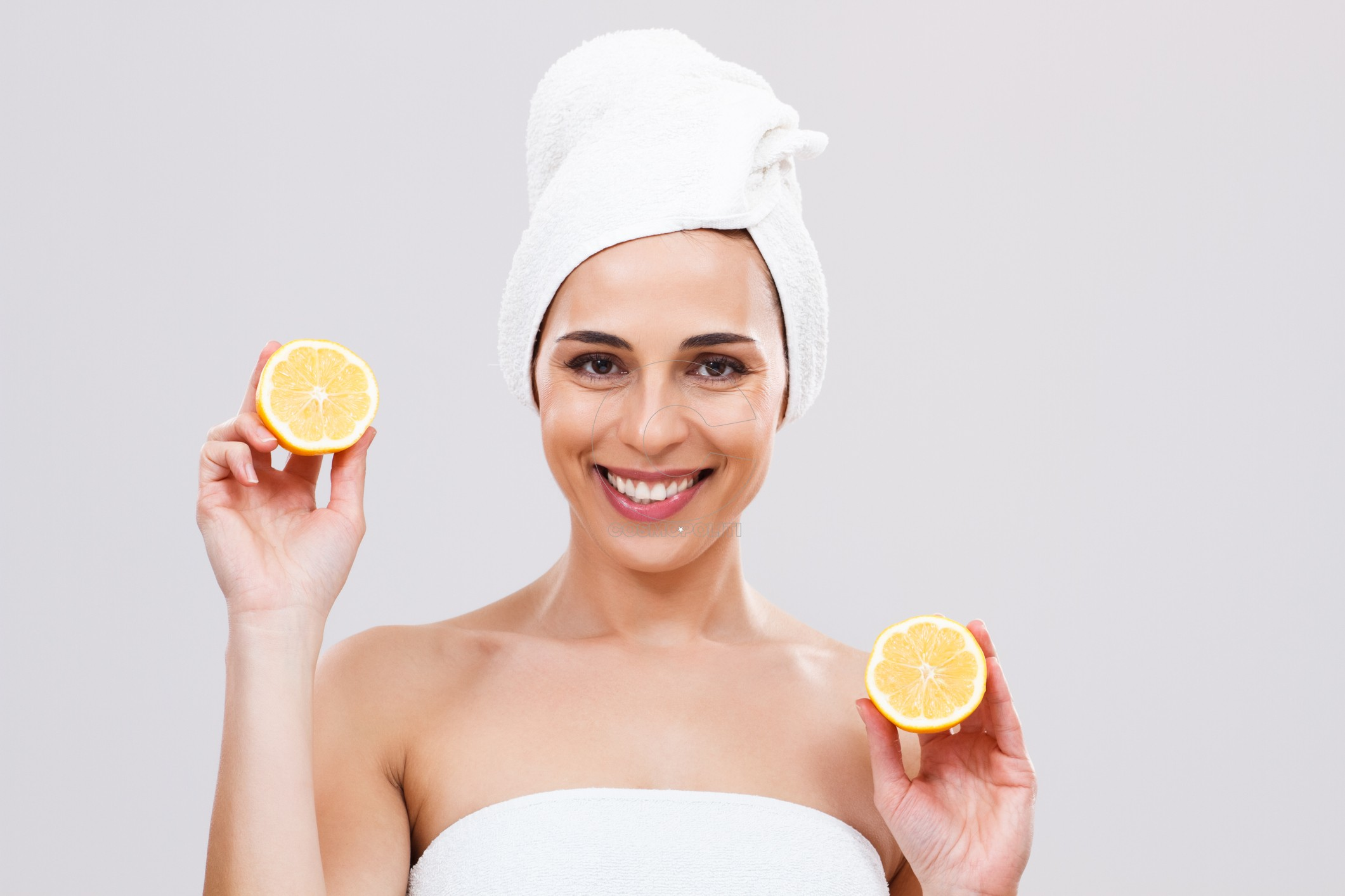 Beautiful woman is holding slices of lemon and looking at camera.