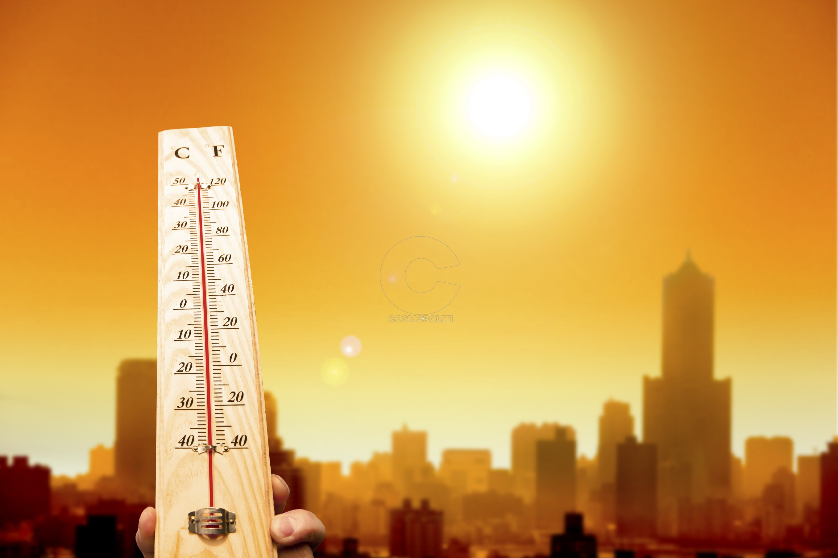 heat wave in the city and hand showing thermometer for high temperature