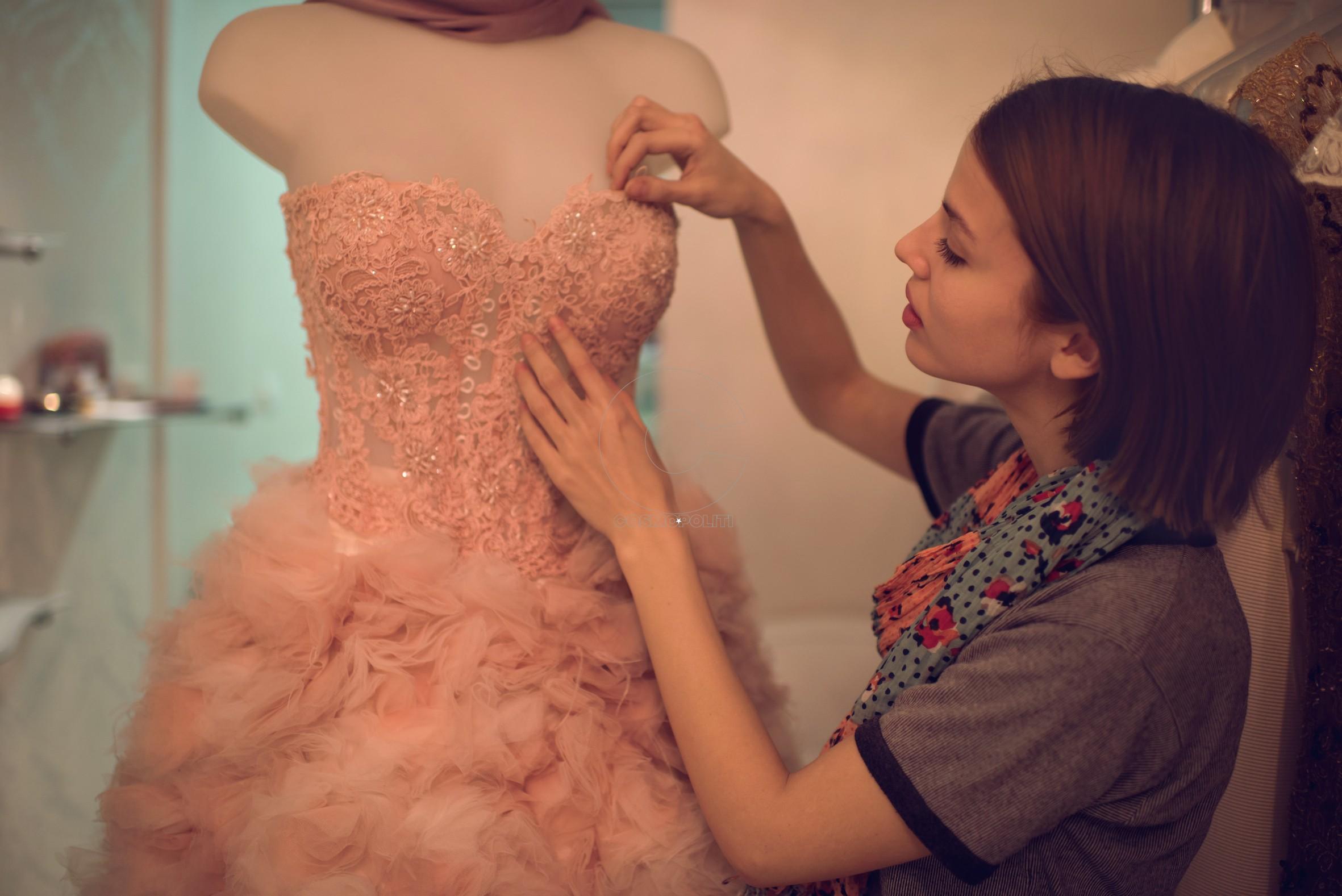 Young clothing designer adjusting dress on mannequin in fashion design studio.