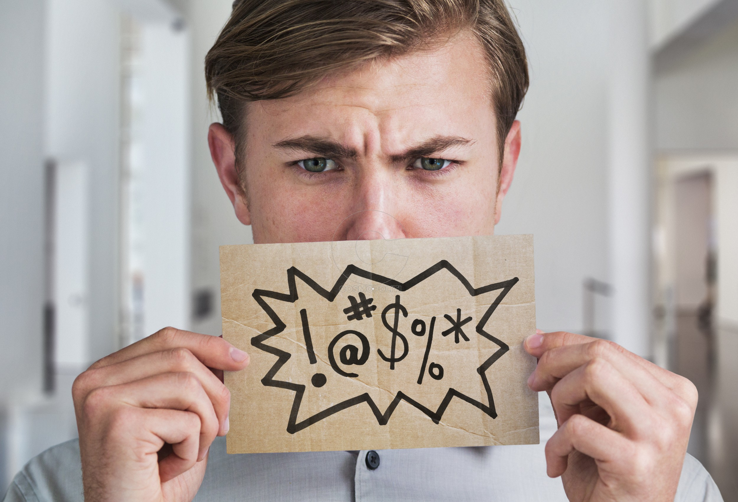 Man holding swear word sign in front of his mouth