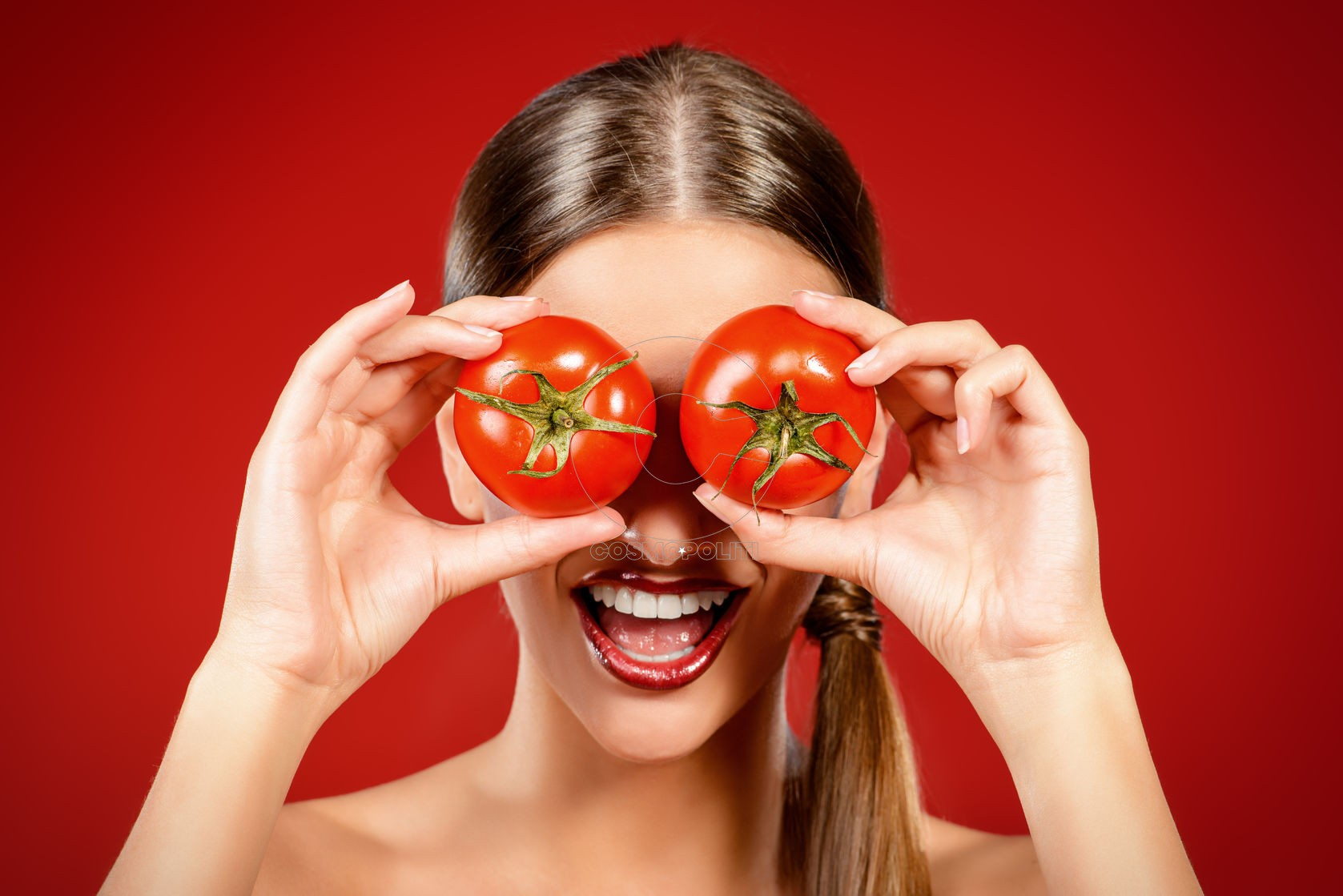 44127357 - beautiful laughing woman holding two ripe tomatoes before her eyes. red background. healthy eating concept. diet.