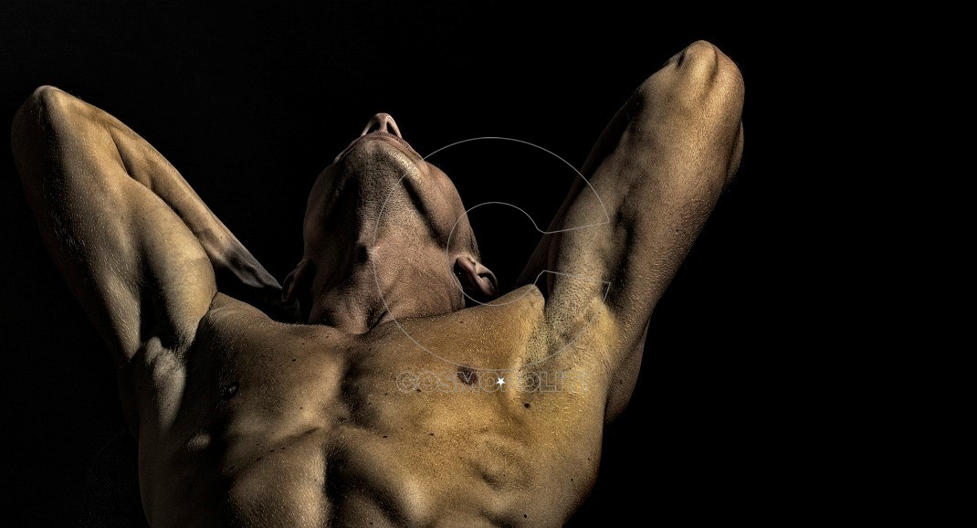 Closeup of one young sexual undressed man with beautiful muscular strong body and torso standing with raised hands in studio on black wall background, horizontal picture