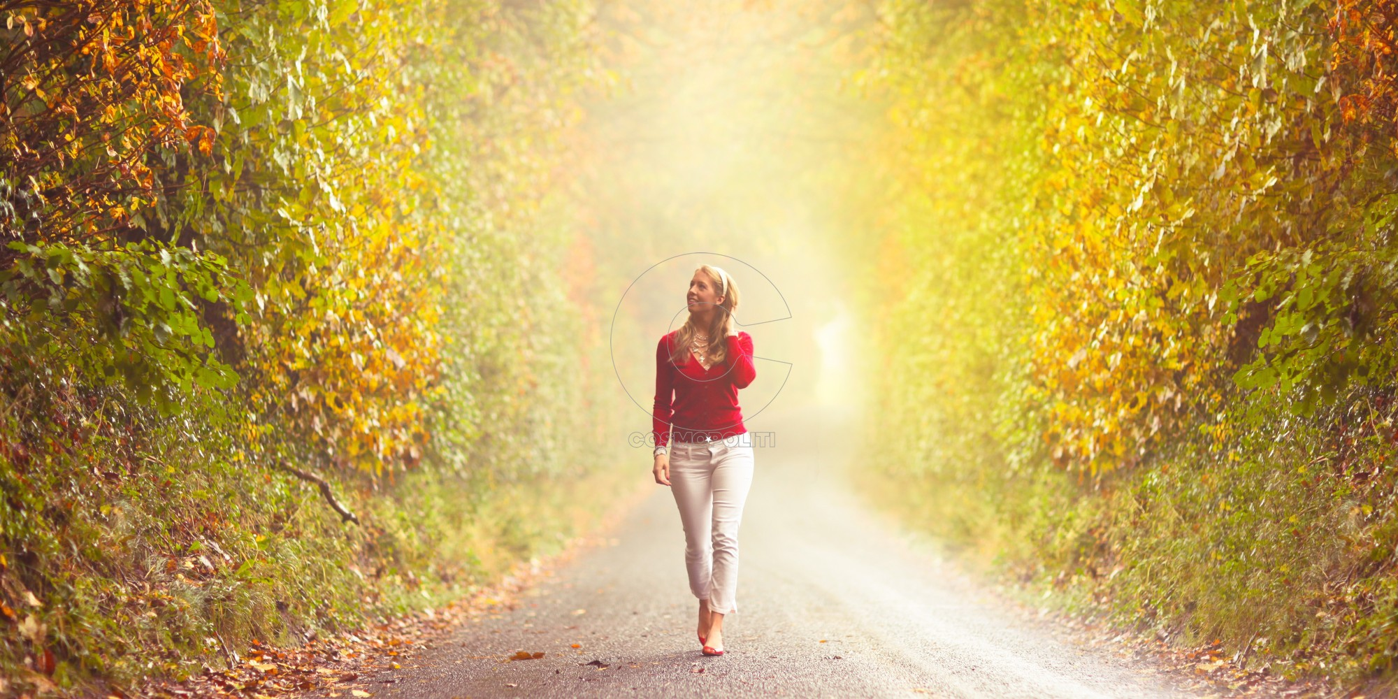 Girl walking in country road in the autumn fog