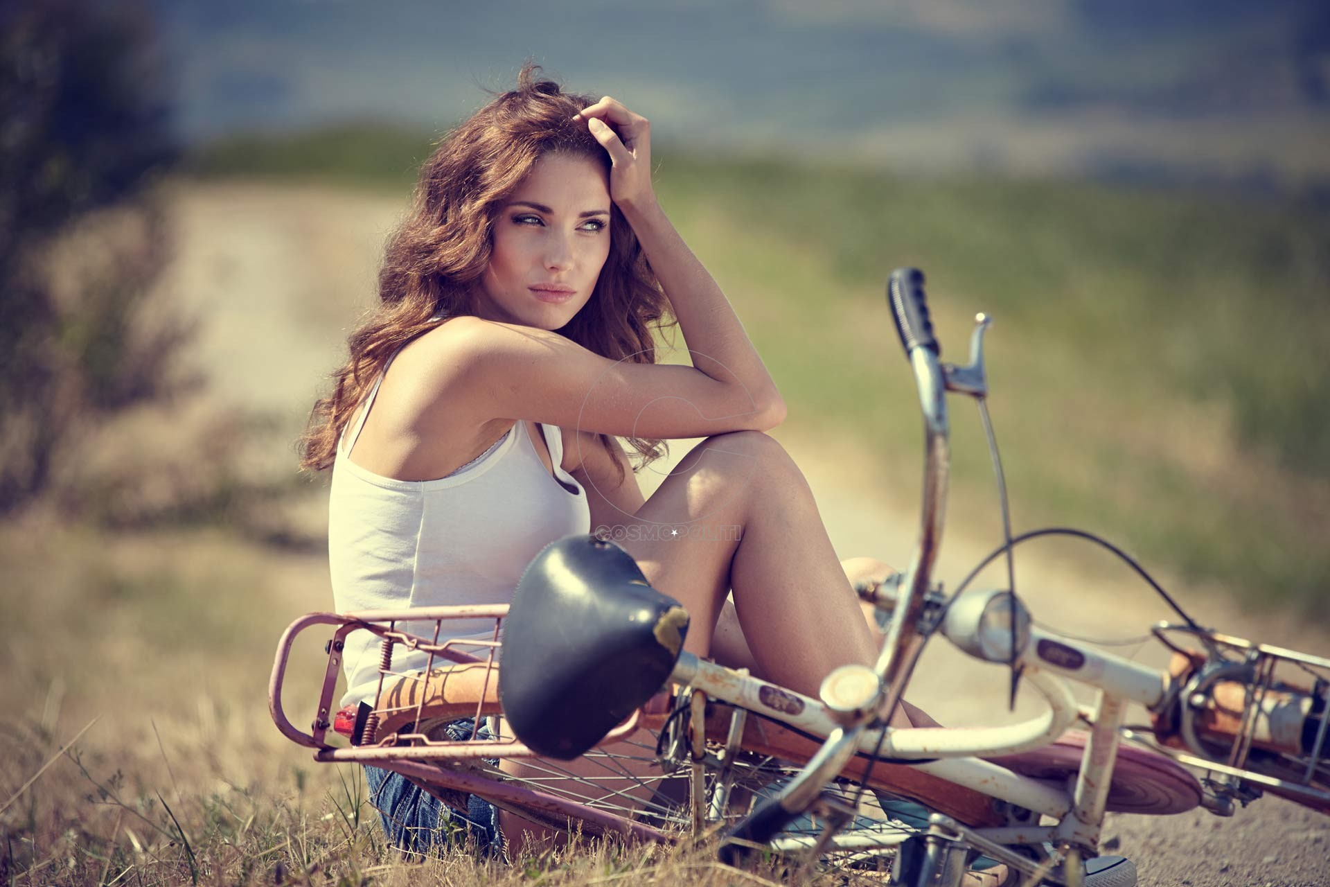 beautiful-vintage-girl-sitting-next-to-bike-summer-time