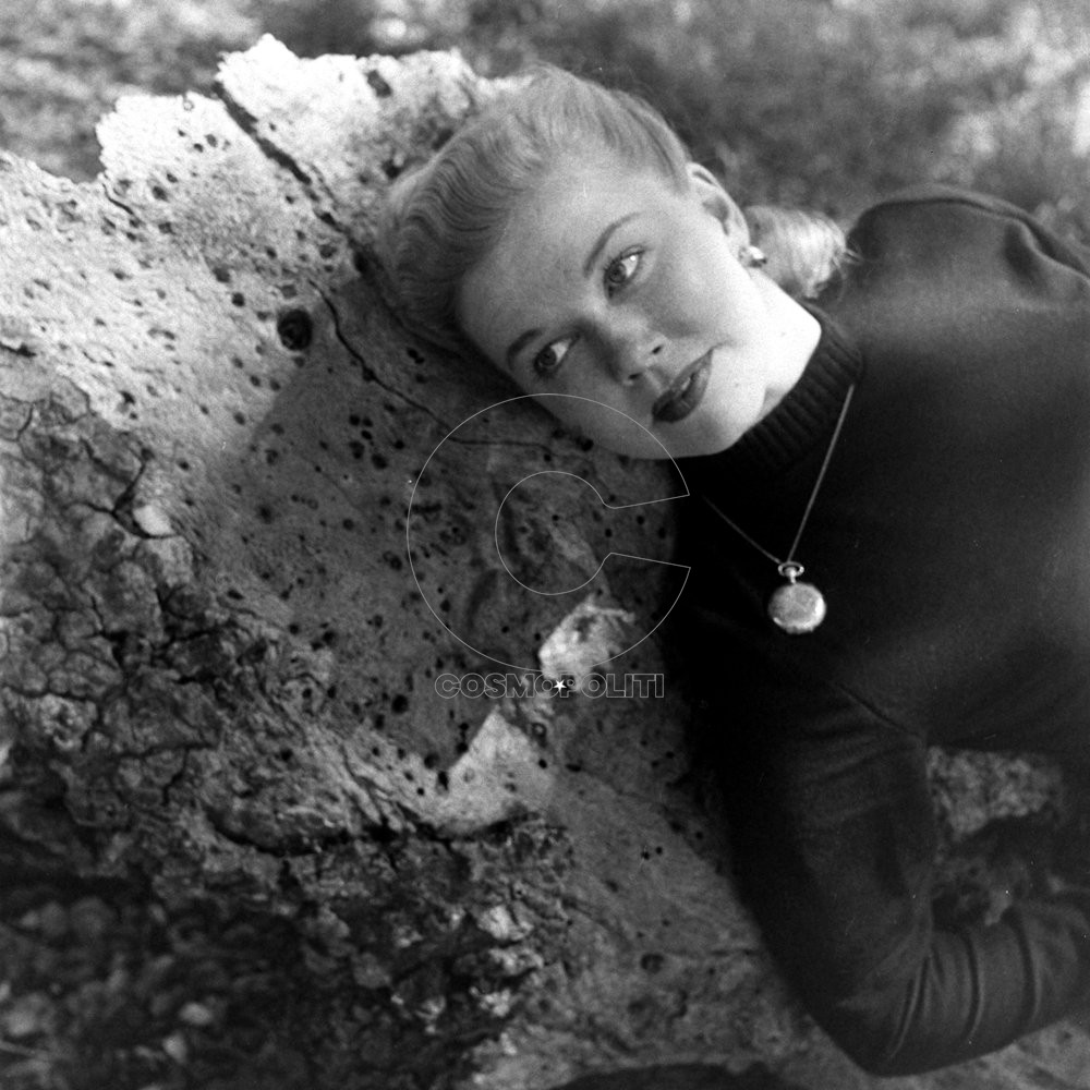 Movie Actress Doris Day leaning against rock.