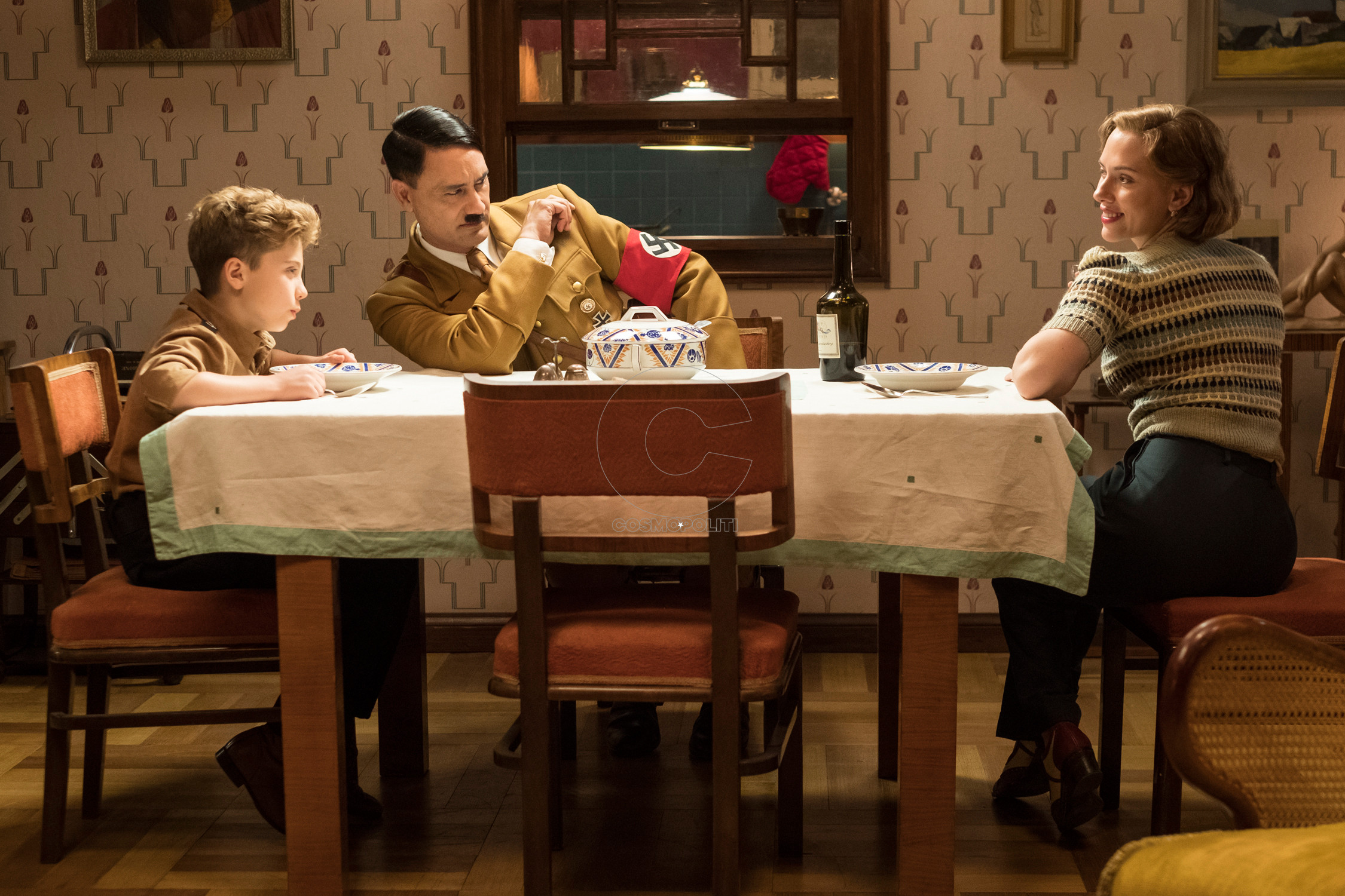 First still from the set of WW2 satire, JOJO RABIT. (From L-R): Jojo (Roman Griffin Davis) has dinner with his imaginary friend Adolf (Writer/Director Taika Waititi), and his mother, Rosie (Scarlet Johansson). Photo by Kimberley French. © 2020 Twentieth Century Fox Film Corporation All Rights Reserved